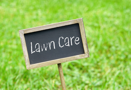 Lawn Care - chalkboard on green grass background Stock Photo