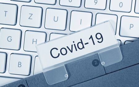 Covid-19 binder on computer keyboard in the office