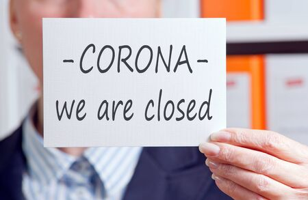 Businesswoman with sign, Corona, we are closed