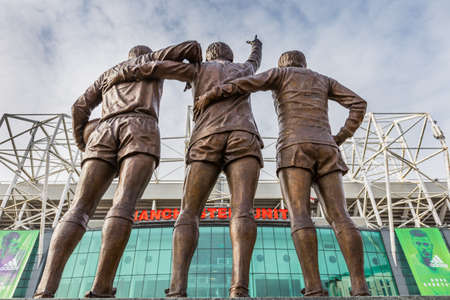Manchester, England - February 27, 2016: On 29 May 2008, to celebrate the 40th anniversary of Manchester Uniteds first European Cup title, a statue of the clubs holy trinity of George Best, Denis Law and Bobby Charlton, entitled The United Trinity, was  新聞圖片