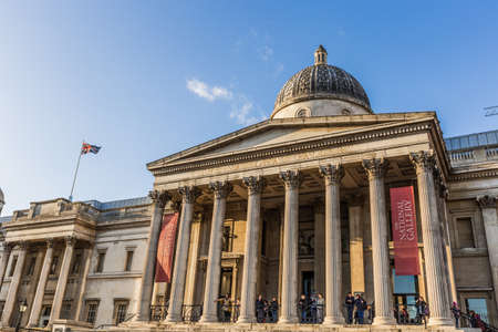 London, UK - March 2, 2016: National Gallery building at Trafalgar square with people in London, UK. Founded in 1824, it houses a collection of over 2,300 paintings dating from the mid-13th century to 1900. 版權商用圖片 - 56610557