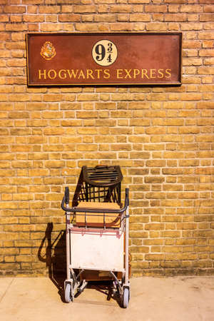 homage: London, United Kingdom - March 3, 2016: This is the British Rail homage to Harry Potter at Kings Cross station in London England. A half trolley is embedded in the wall and tourists take pictures of themselves pretending to exit through the wall for the H Editorial
