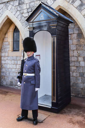 Windsor, United Kingdom - March 4, 2016: A guard outside Windsor Castle, close to the Guard house on the grounds inside the castle walls. The Guard is standing at attention and holding a rifle. Windsor Castle is one of the official residences of the Briti 新聞圖片