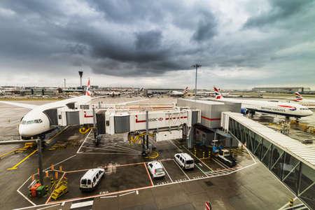 London, United Kingdom - March 5, 2016: British Airways jumbo jet aeroplanes at Heathrow Terminal 5 on a stormy day.British Airways is the flag carrier airline of the United Kingdom and the largest airline in the United Kingdom based on fleet size. 版權商用圖片 - 56610573
