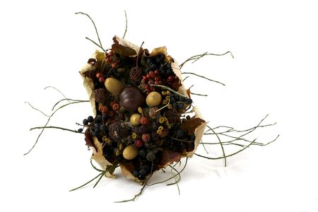Isolated colourful bouquet of dry flowers, chestnuts, acorns and rowan on white