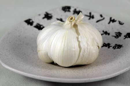 Isolated, white, fresh garlic on ceramic, small plate on white