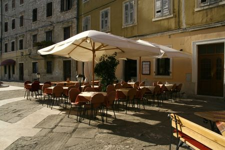 Street restaurant in old Mediterranean city at the early morning