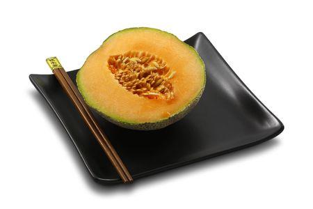 Fresh, ripe melon served on stylish, black plate with chopsticks, on white, isolated Stock Photo