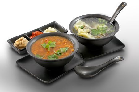 Delicious, first course dinner for two served in stylish, black bowls with spicy starters on white, isolated Stock Photo