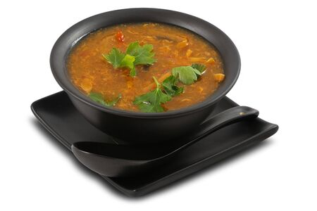 Tasty vegetable soup served in stylish, black bowl, on white, isolated