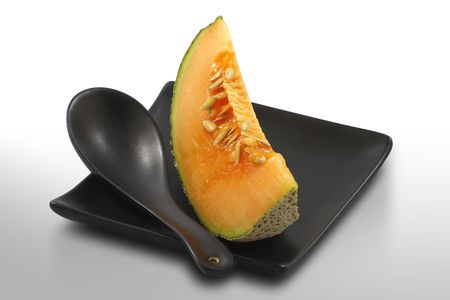 Fresh, ripe melon served on stylish, black plate, on white, isolated