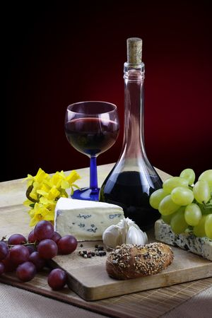 entre:  dinner with cheese, wine, grapes and jonquils on rustic board Stock Photo