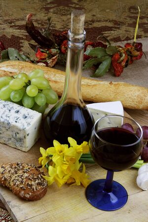 dinner with cheese, wine, grapes and jonquils on rustic board Stock Photo