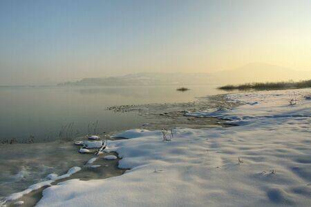 Sunny, a bit foggy, winter morning at the lake Stock Photo