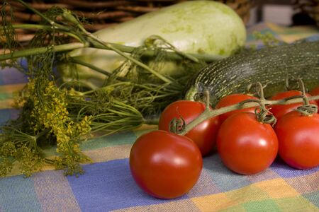 Cherry-tomatoes surrounded by other vegetables on the colorful tablecloth Stock Photo