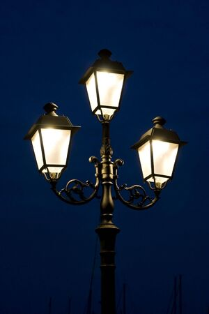 Old, stylish, multi-branch street lamp at the night