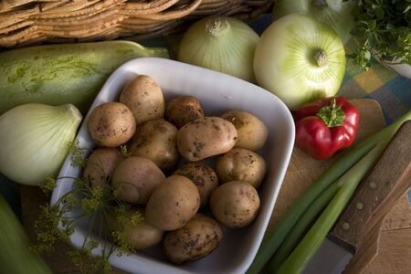 Dish of young, fresh potatoes and other vegetables on the rustic desk