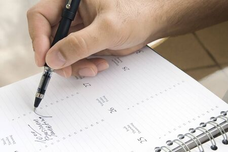 Man writing down the date of business meeting