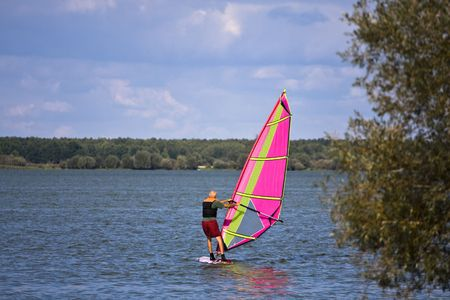 Man learning how to surf on the quiet lake