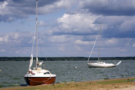 Two, small yachts at the sandy lakeside Stock Photo