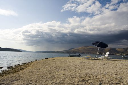 Lonely umbrella on the beach, after season
