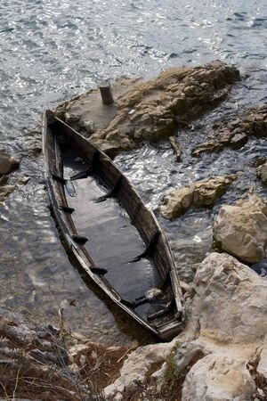Sunken, old boat at the rocky shore Stock Photo