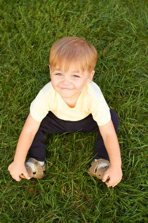 Sonriendo ni�o sentado en la hierba fresca