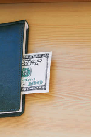 Hundred dollar bill lying in the notebook photo