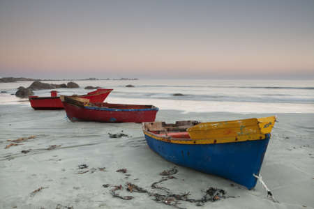 dingy: Three small fishing boats on a beach at dusk