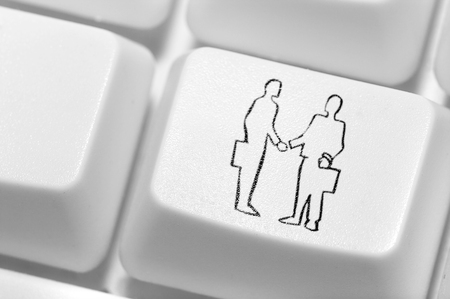 The button with an emblem of hand shake of two businessmen on the keyboard.  Stock Photo