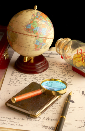 The globe, magnifier with a notebook and the old manuscript. Stock Photo - 1482324