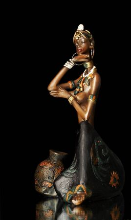 adult kenya:  Figurine of the African girl on a black background...
