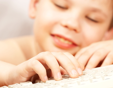 The boy with the keyboard at a computer photo