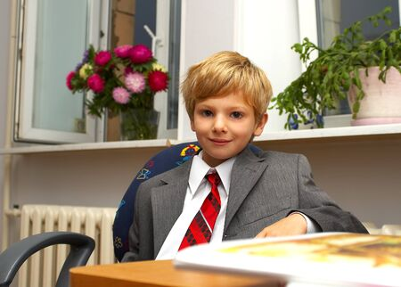 director de escuela: El muchacho en un traje detr�s de un escritorio  Foto de archivo