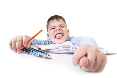lazybones: The boy with the book behind a table on a white background Stock Photo
