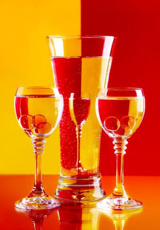 rainbow cocktail: Bicchieri di vino con l'acqua su un fondo giallo e rosso.