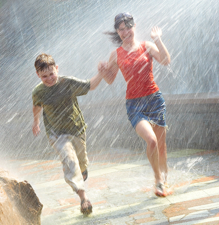 The girl with the boy run under a down-pour rain