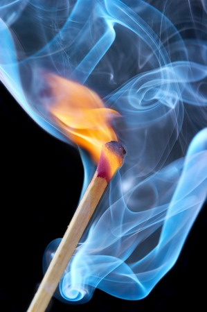 Photo of a burning match in a smoke on a black background photo