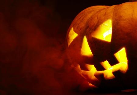 hollows: A scary old jack-o-lantern on black.  Stock Photo