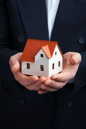housing style: Hand of the businessman with the house