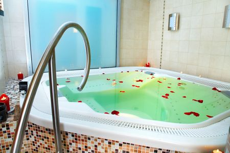 Bathtub with petals of roses Stock Photo