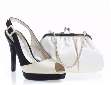 Female shoes and handbag on it is white a background