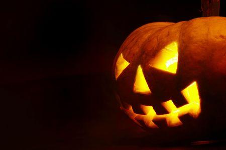 A scary old jack-o-lantern on black. photo