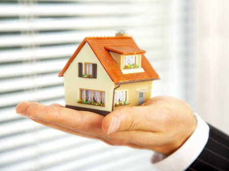 insurance agent: The house in human hands Stock Photo