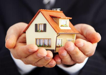 housing style: Hand of the businessman with the house... Stock Photo