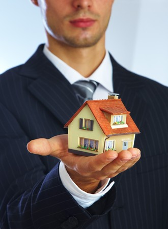 hypothec: Hand of the businessman with the house... Stock Photo