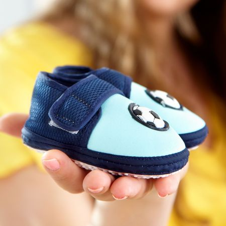 baby's bootee: babys bootee on a palm of future mum Stock Photo