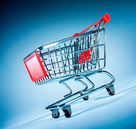 Empty shopping cart on the blue photo