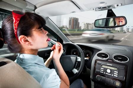 women make up lips at the wheel the car photo