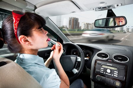 women make up lips at the wheel the car photo